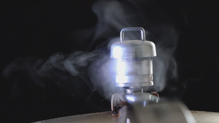 Pressure cooker valve releasing steam