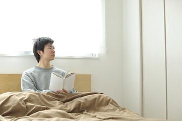 ベッドの上で眠そうにしているパジャマ姿の男性