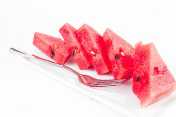 Arange piece of fresh watermelon on dish with fork isolated on w