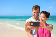 Smartphone - beach vacation couple taking selfie