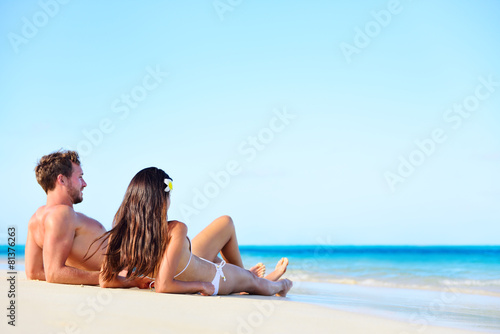 Beach vacation couple relaxing tanning in summer - 81376263