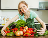 Portrait of happy woman with pile of vegetables