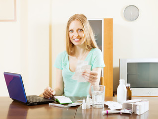 Positive  woman reading about medications in laptop