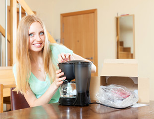 Happy young woman with new coffee machine at home
