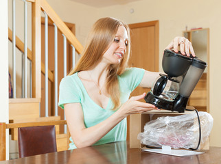 woman unpacking and reading manual for new coffeemaker at home i