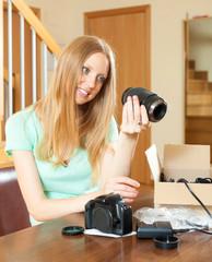 Smiling young  girl unpacking new digital camera  in home interi