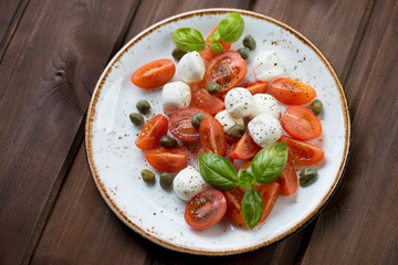 Caprese salad with capers, dark wooden surface, high angle view