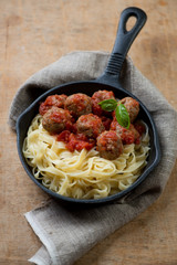 Cast-iron pan with meatballs in tomato sauce and tagliatelle