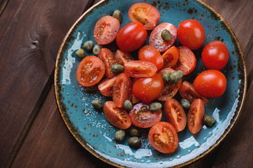 Above view of cherry tomatoes with capers, sea salt and pepper