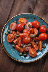 Sliced tomatoes with capers, sea salt and pepper, above view