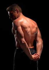 Rear view of shirtless sportsman demonstrating back muscles