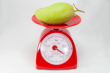 Fresh Green mango on weight scale isolated on white