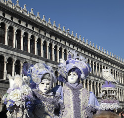 masked persons in ornate costume on San Marco Square, Venice