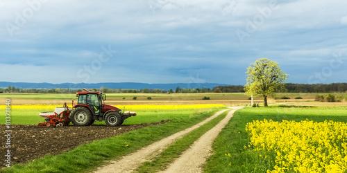 Leinwandbild Motiv Traktor auf dem Feld bei der Arbeit