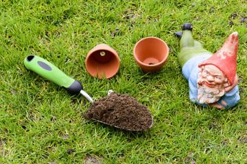 Alter Gartenzwerg und Pflanzutensilien