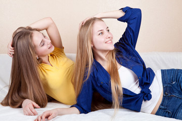 Two beautiful girlfriends lie on the couch. teens