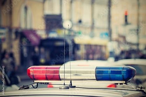 the police car patrols city streets - 81380643