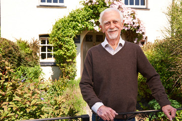 Senior Man Standing Outside Pretty Cottage