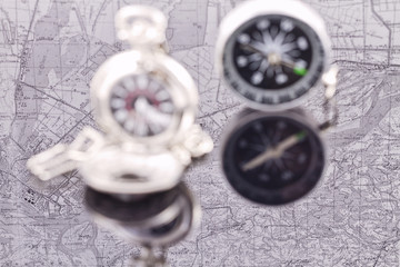 compass and a silver pocket watch on the background reflection m