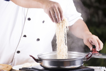Chef putting the noodle to the pot