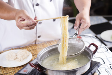 Chef holding colander with cooked Noodle