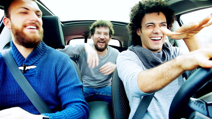 Three cool men laughing and dancing in car happy
