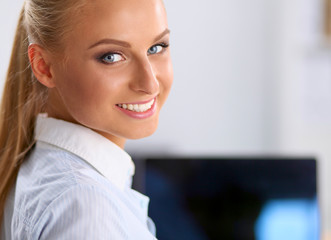 Attractive businesswoman sitting on a desk with laptop in the