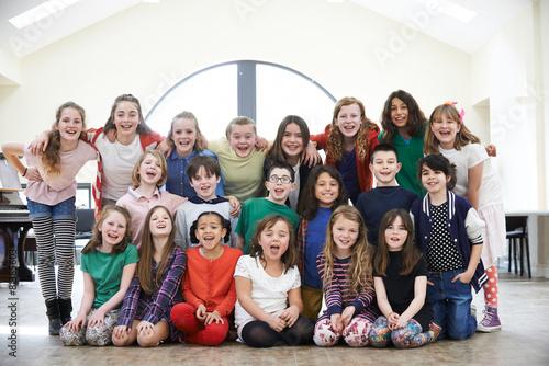 Large Group Of Children Enjoying Drama Workshop Together - 81385603