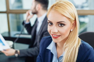 Beautiful young businesswoman posing with a smile in office with