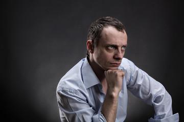 Serious man sits thinking