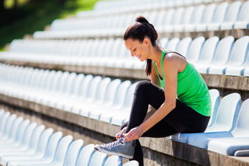 Young woman tying a shoelace before jogging