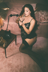 Woman in Lingerie Leaning on Bed Putting Makeup