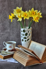 Still life with an open book and daffodils.