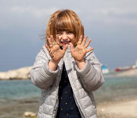 Bambina in spiaggia con le mani sporche