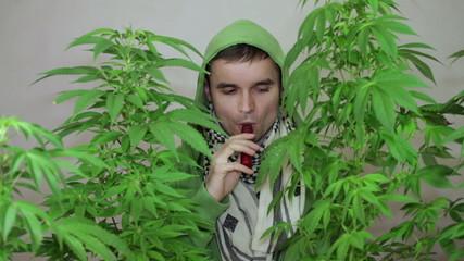 Young man in green hoodie smoking Marijuana with vaporizer.