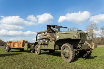 Military jeep pulling trailer carrying wooden boxes with bullets