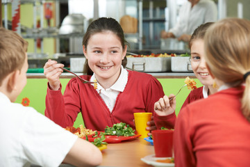 Group Of Pupils Sitting At Table In School Cafeteria Eating Lunc