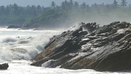 big waves crashing on stone beach