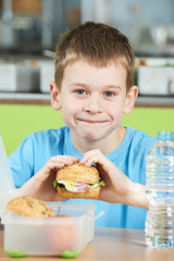 Male Pupil Sitting At Table In School Cafeteria Eating Healthy P