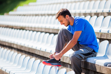 Young man tying a shoelace before jogging