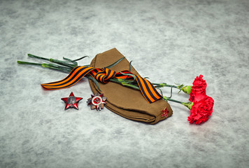 Carnation flowers, George Ribbon, forage cap, orders and medals