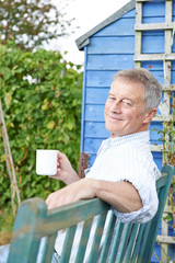 Senior Man Relaxing In Garden With Cup Of Coffee