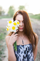 Red-haired young lady with bouquet of daffodils at countryside