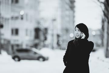 冬の街角でスマートフォンで話す女性