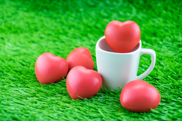 Red heart in coffee cup on grass, Love concept