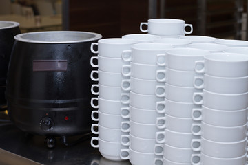 Stack of white soup bowls and soup heater