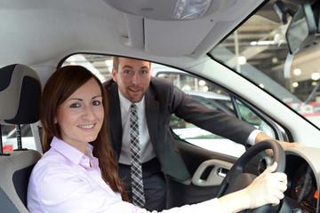 Frau testet auto im Autohaus, im Hintergrund Verkäufer