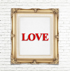 """Love"" word in golden vintage photo frame on white brick wall,Lo"