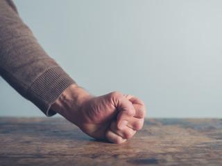Man slamming his fist on table