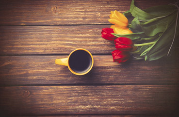 Cup of coffee and tulips on wooden table.
